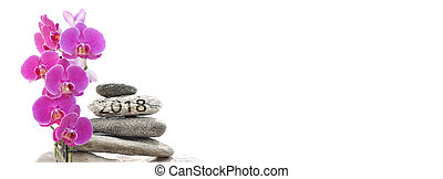 orchid and 2018 written on pebbles stacked on white...
