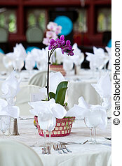 A purple orchid flower centerpiece on a white wedding table