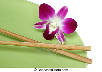 Orchid on green plate with chopsticks