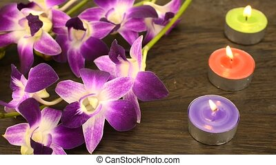 Orchid flowers and candles - Purple orchid flowers and three...