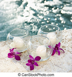 Three candles and three purple orchids by pool.