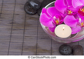 bowl with orchids and candle and massage black stones