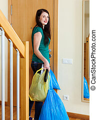 girl tossing out the garbage at home