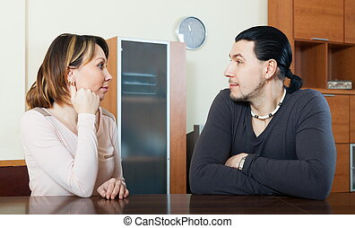 Ordinary couple talking in home interior