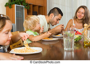 family of four eating spaghetti