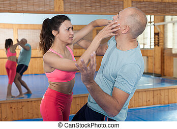 Ordinary female is fighting with trainer on the self-defense course for woman in sport club