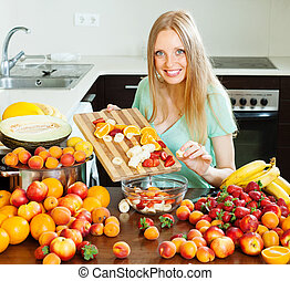 Ordinary long-haired girl cooking fruit salad