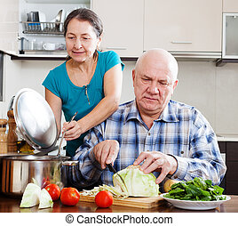 Ordinary senior couple cooking with vegetables