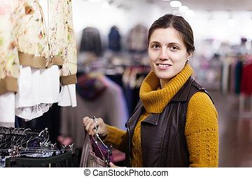 woman choosing skirt at clothing store