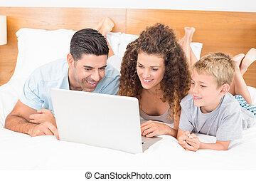 ordinateur portable, utilisation, lit, ensemble, famille, heureux