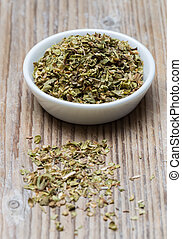 Oregano in a bowl on wood