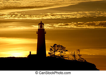 Dramatic skies during a sunset silhouettes Yaquina head lighthouse.