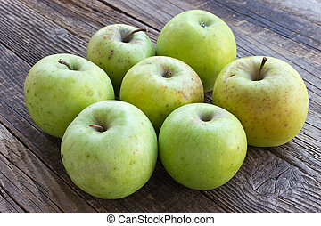 Organic apples on wooden background