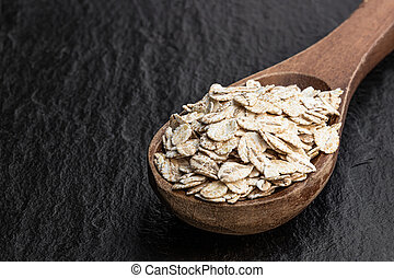 Organic barley flakes in wooden spoon on black stone background