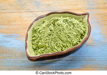 organic barley grass powder in a leaf bowl