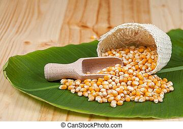 Organic corn drop out of sackcloth on banana leaves