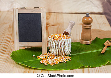 Organic corn drop out of sackcloth on banana leaves with small blackboard