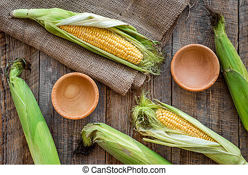 Organic farm food. Fresh corn on rustic wooden table top view
