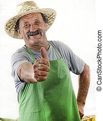 organic farmer with a green apron raises his thumb