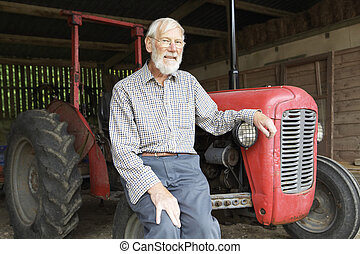 Organic Farmer Sitting Next To Old Fashioned Tractor