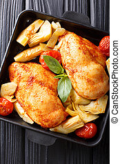 Organic food: a serving of chicken breast with artichokes and tomatoes close-up. Vertical top view