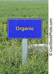 Organic food label on the pole on the field.
