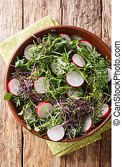 Organic food radish salad with micro green mix close-up in a bowl. Vertical top view