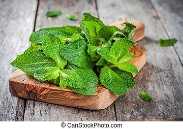 organic fresh bunch of mint on wooden cutting board