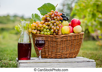 Organic fruit in basket in summer grass. Decanter and glass of wine.