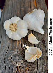 Organic garlic whole and cloves on the old wooden background
