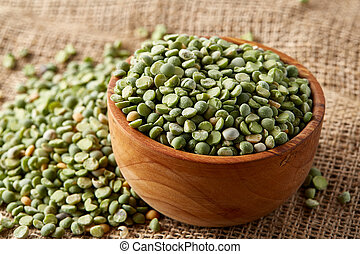 Organic green peas in a bowl on burlap tablecloth, close-up, top view, selective focus, shallow depth of field.