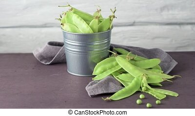 Organic Green Sugar Snap Peas Ready to Eat on cement background. Rotating slide.