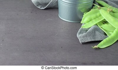 Organic Green Sugar Snap Peas Ready to Eat on cement background. Slide from left.