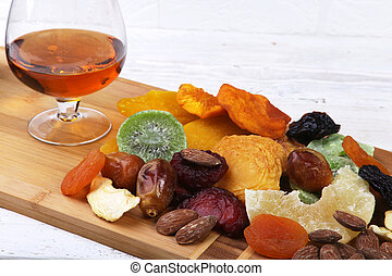Organic Healthy Assorted Dried Fruit and glasses with cognac or whiskey on wine board. Selective focus.