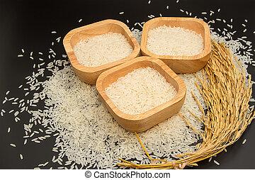 organic jasmine rice in wooden bowl on white background