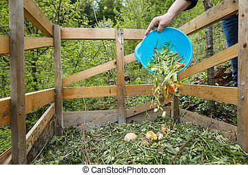 Organic kitchen waste being thrown on a compost
