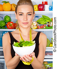 Closeup portrait of cute serious woman with measure tape and fresh vegetables salad, refrigerator full of vegetables, sportive trainer, organic food, health and beauty care concept
