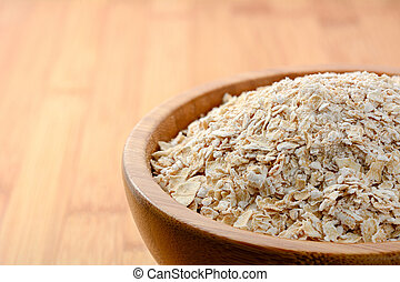 Organic oat flakes in wooden bowl