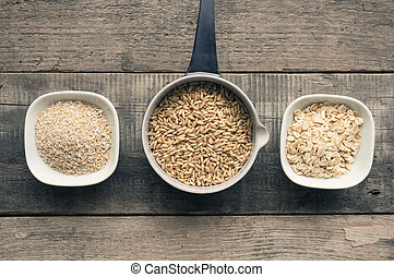Organic oat grain, oat meal and oat bran on a rustic wooden ...