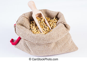 Organic oat grains in jute bag, healthy nutrition, white background