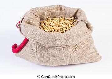 Organic oat grains in jute bag on white background