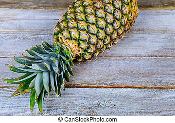 organic Pineapple placed on a wooden table.