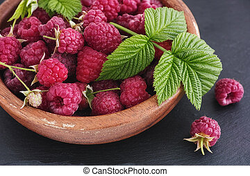 Organic raspberries in a wooden bowl