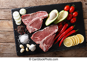 Organic raw t-bone beef steak with ingredients close-up. horizontal top view