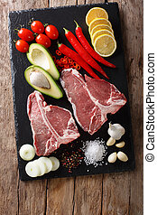 Organic raw t-bone beef steak with ingredients close-up. Vertical top view