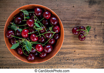 ripe cherries with leaves in bowl on old wooden rustic backgroun