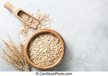 Organic rolled oats in wooden bowl on concrete background