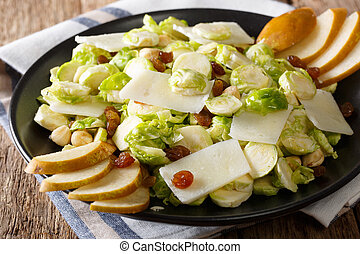 Organic salad from Brussels sprouts with hazelnuts, cheese, raisins and pears. horizontal