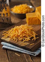 Organic Shredded Sharp Cheddar Cheese on a Cutting Board