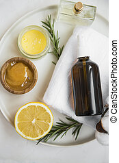 Organic skincare ingredients with towel, face mist and manuka honey, natural treatments ingredients with lemon, honey, balm salve, rosemary herb, spa still life setting
